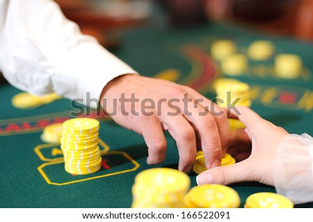 female hand trying to take casino chips