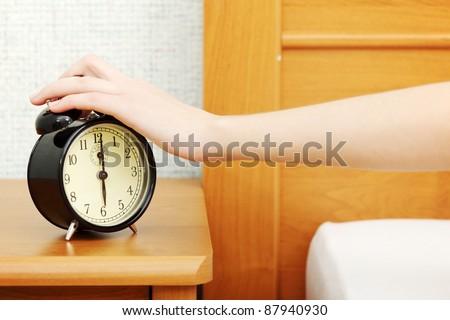 Female hand turning off alarm clock. - stock photo