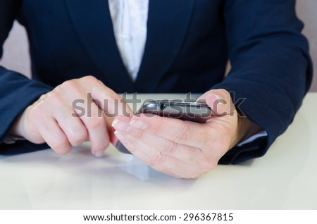 female hand typing into mobile phone behind working desk