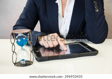female hand typing into tablet behind working desk