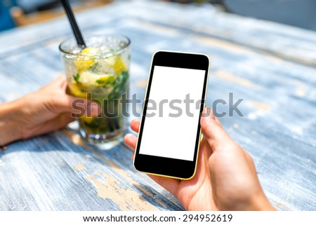 Female hand using a phone with isolated screen on wooden vintage table holding a glass with mohito - stock photo