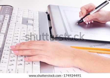 Female hand using graphics tablet on table close up - stock photo