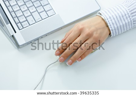 Female hand using mouse and laptop computer. - stock photo