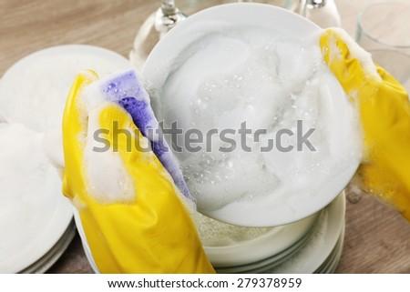 Female hand washing dish close up - stock photo