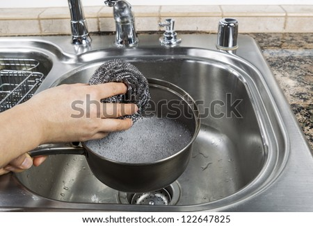 Female hand washing stainless steel pan with steel pad and soapy water in kitchen sink - stock photo