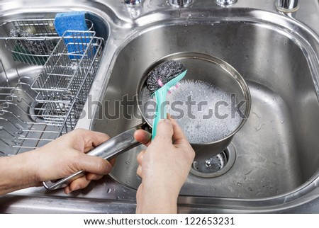 Female hand washing stainless steel pan with steel pad brush and soapy water in kitchen sink - stock photo