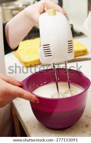 female hand whisk the cream with a mixer - stock photo
