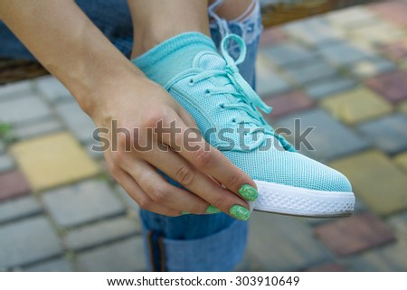 Female hand wipe cloth shoes outdoors. A young woman sits on a bench and cleans her shoes from dust. - stock photo