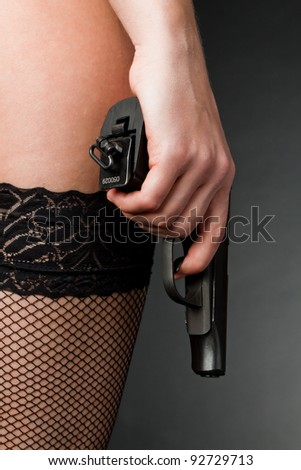 Female hand with a gun on a dark background in stockings - stock photo