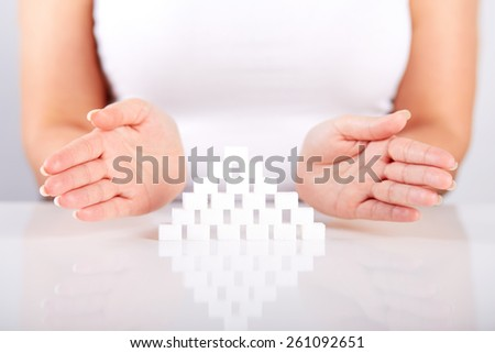 Female hand with a pyramid of sugar cubes - stock photo