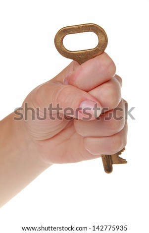 Female hand with an old metal key on a white background - stock photo