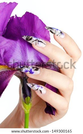 Female hand with beautiful nails over a violet flower, on a white background. - stock photo