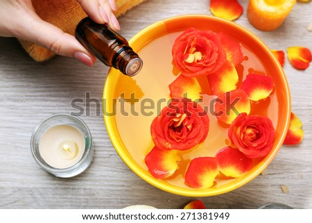 Female hand with bottle of essence and bowl of aroma spa water on wooden table, closeup - stock photo
