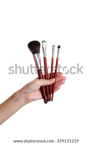 Female hand with brushes for make-up isolated on white