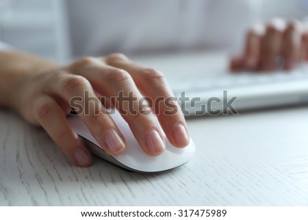 Female hand with computer mouse on table, closeup - stock photo