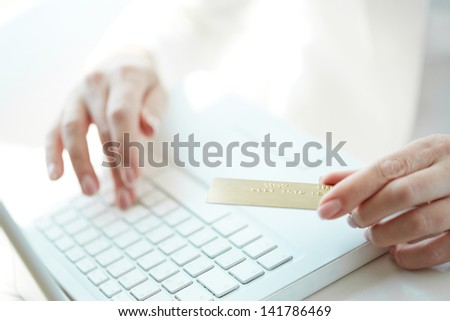 Female hand with credit card during shopping through Internet - stock photo