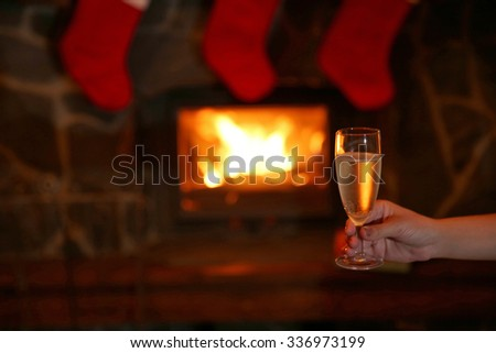Female hand with glass of sparkle wine on fireplace background - stock photo