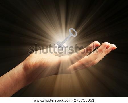 Female hand with key on dark background - stock photo