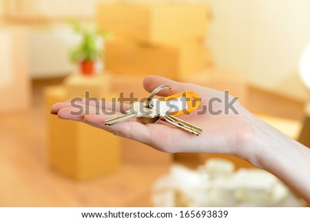 Female hand with keys ob stack of cartons background: moving house concept  - stock photo