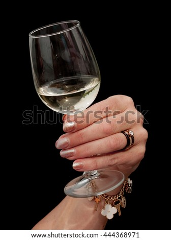 Female hand with manicured glitter nails holding a glass of white wine against a  black background