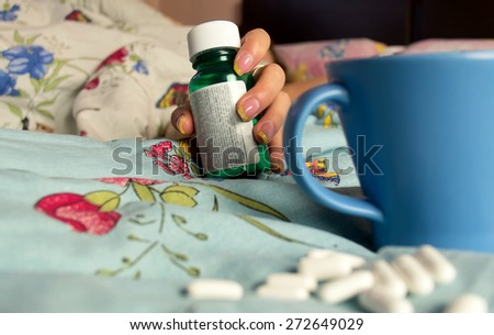 Female hand with medications pill bottles and spilled pills in the blurred foreground - stock photo