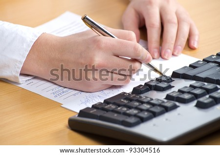 Female hand with pan writing on the paper nearkeyboard on the table - stock photo