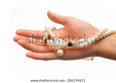 female hand with pearl jewelry