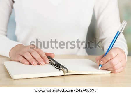 Female hand with pen and notebook at wooden desktop on light background