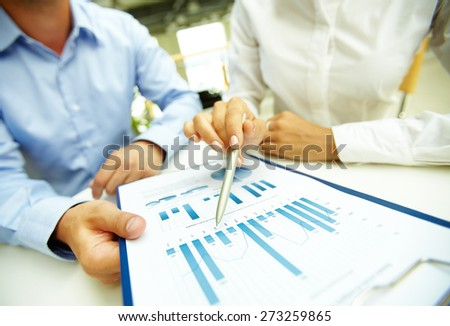 Female hand with pen pointing at document  - stock photo