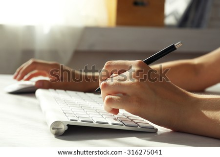 Female hand with pen typing on keyboard at table, closeup - stock photo