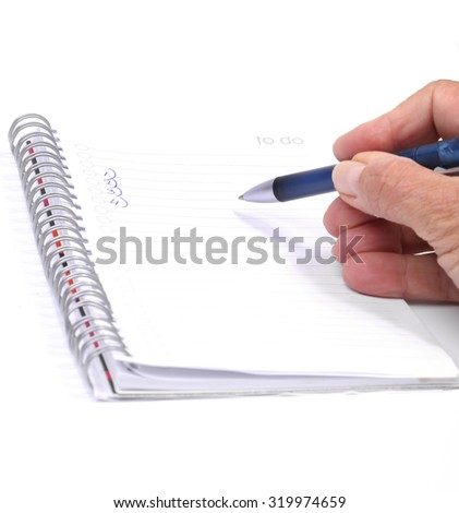 Female hand with pen writing in notebook - stock photo