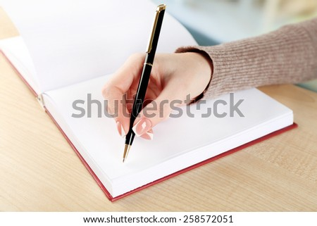Female hand with pen writing on notebook, closeup - stock photo
