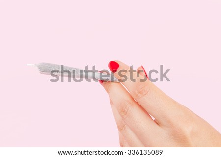 Female hand with red fingernails holding cannabis joint isolated on pink background. Female marijuana abuse. - stock photo