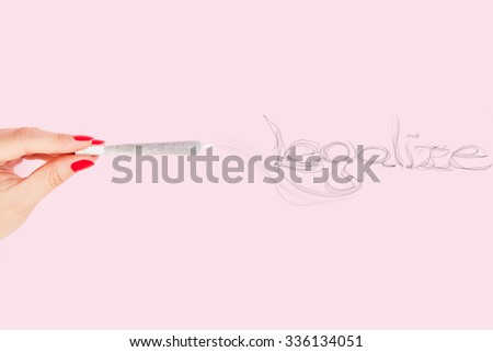 Female hand with red fingernails holding cannabis joint, smoke forming the word legalize isolated on pink background. Cannabis abuse. - stock photo