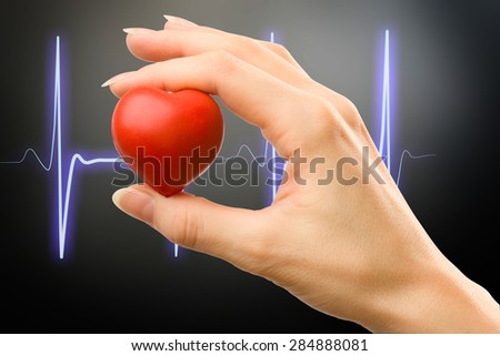 Female hand with red heart carefully holding - stock photo