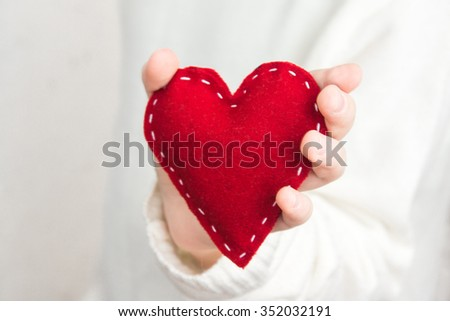Female hand with red heart over white background, close up
