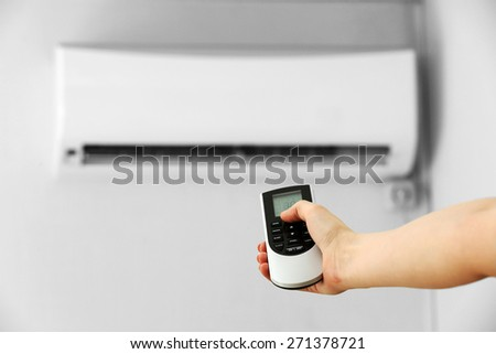 Female hand with remote control directed on conditioner, indoors - stock photo