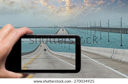 Female hand with smartphone taking a picture of Keys Islands Interstate, Florida. Tourism concept. - stock photo