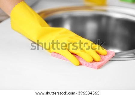 Female hand with sponge cleaning a sink in the kitchen