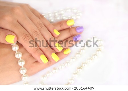 Female hand with stylish colorful nails and beads, on light background - stock photo