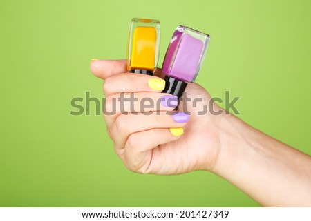 Female hand with stylish colorful nails holding bottle with nail polish, on green background - stock photo