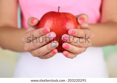 Female hand with stylish colorful nails holding red apple, close-up, on color background - stock photo