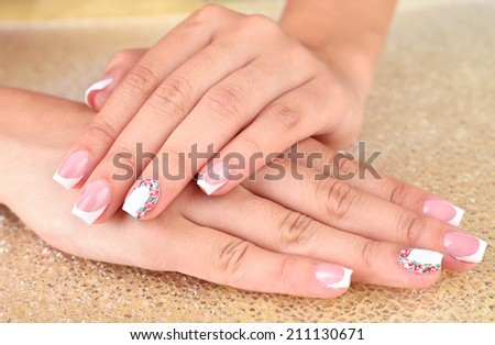 Female hand with stylish colorful nails on bright background