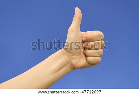 Female hand with the thumb lifted in top against the dark blue sky