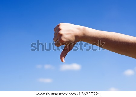 Female hand with thumbs down over blue sky - stock photo