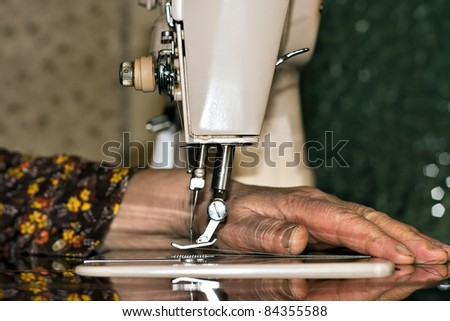 female hand working on the sewing machine - stock photo