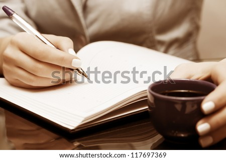 Female hand writing in a notebook - stock photo