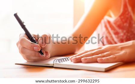 Female hand writing in notebook at th kitchen table - stock photo