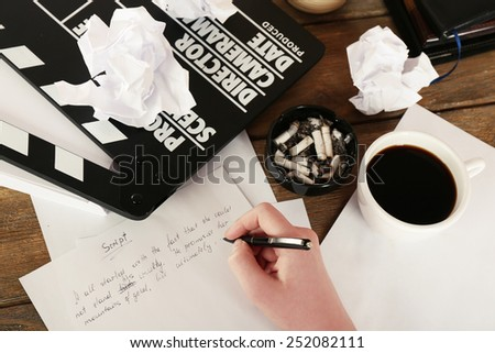 Female hand writing script at desktop with moving clapper and sheets of paper background - stock photo