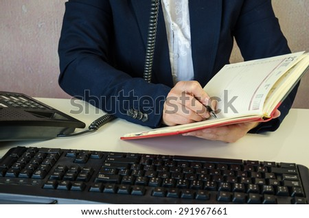female hand writing with pen into notepad and phoning - stock photo